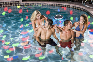 Two couples in swimming pool at night